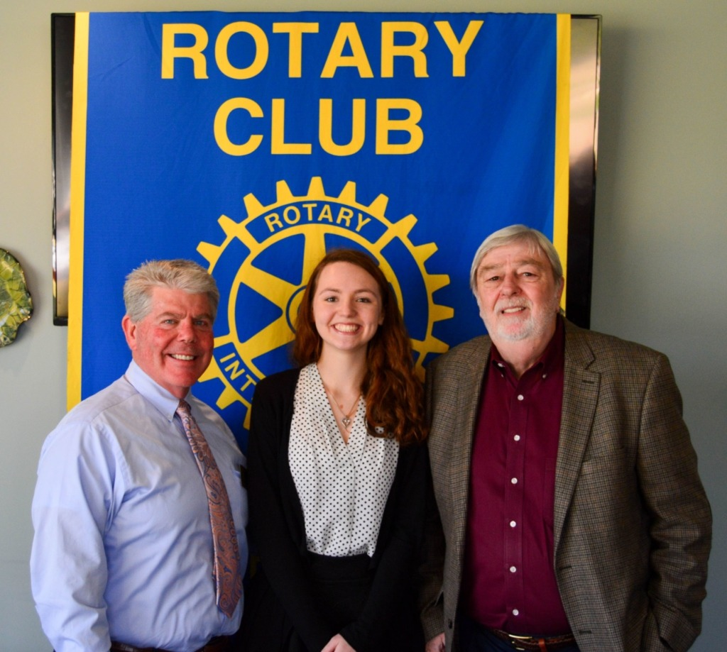 female STAR student posed with two men in front of Rotary Club banner