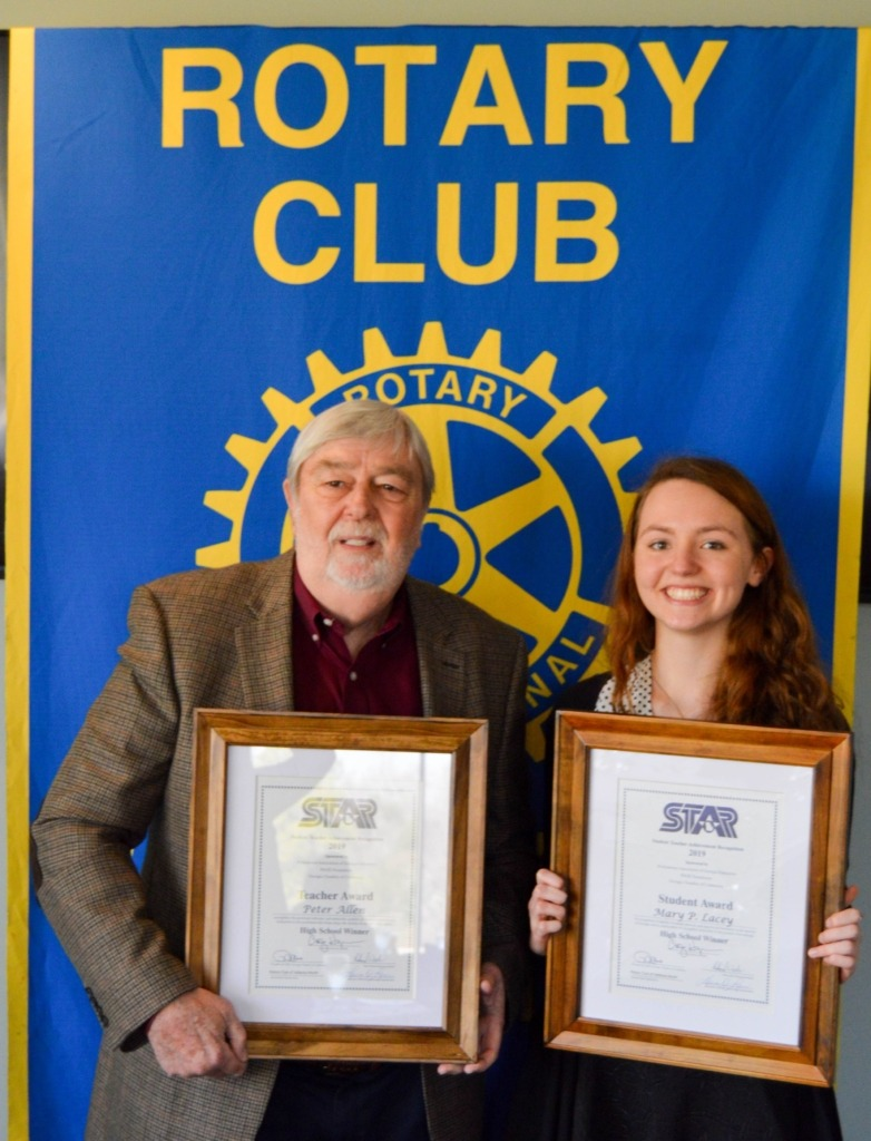 female STAR student and male STAR teacher in front of Rotary Club banner